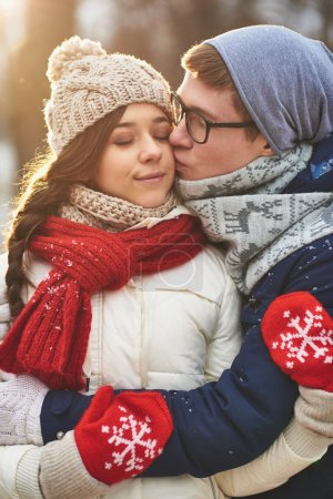 Man kissing  girlfriend on cheek