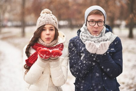 Young couple blowing snowflakes