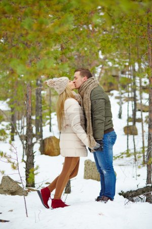 Couple kissing in winter forest