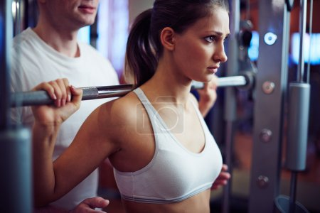 Photo for Young woman training with barbell in gym with instructor - Royalty Free Image