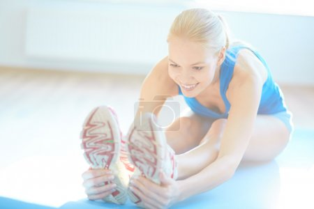 Photo pour Fit femme faire de l'exercice d'étirement dans la salle de gym - image libre de droit