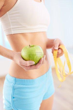 Photo pour Fit femme tenant pomme verte et ruban à mesurer dans les mains - image libre de droit