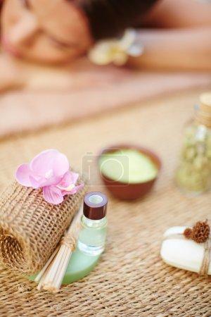 Photo pour Objets cosmétiques avec une femme détendue sur fond de salon spa - image libre de droit