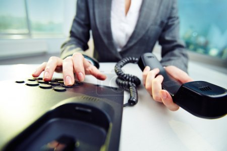 Businesswoman dialing phone number