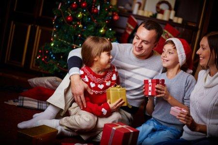 Photo pour Portrait de famille conviviale avec cadeaux soirée de Noël à la maison - image libre de droit