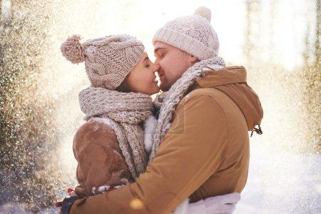 Loving couple kissing in snowfall