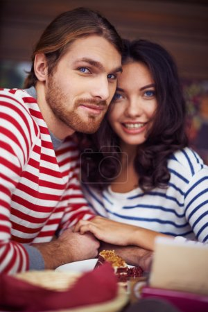 Photo for Amorous dates looking at camera sitting in cafe - Royalty Free Image