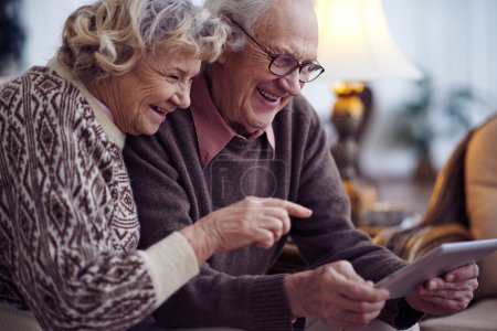Elderly man and woman using touchpad