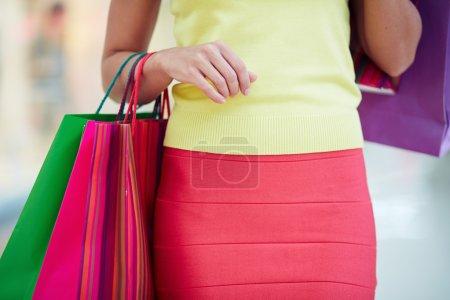 Photo pour Femme client dans smart casual portant des sacs de papier colorés - image libre de droit