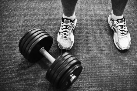 Man in sneakers and barbell