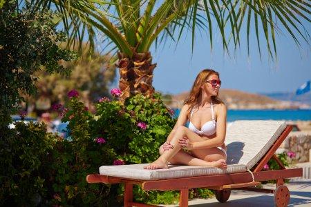 Woman sunbathing on deckchair