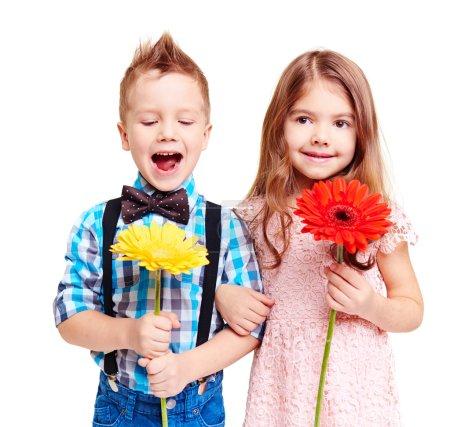 Photo pour Portrait de couple mignon d'enfants avec des fleurs dans les mains - image libre de droit