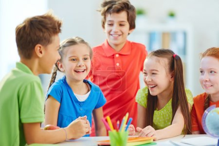 Photo for Friendly boys and girls talking and laughing at break in school - Royalty Free Image