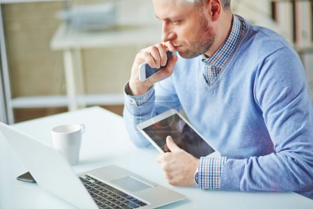 Photo for Pensive businessman working with multi-media gadgets in office - Royalty Free Image