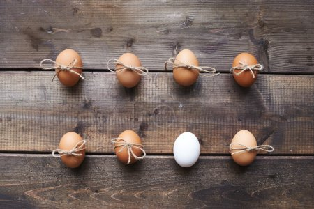 Photo for Two rows of eggs tied by threads on wooden background, top view - Royalty Free Image