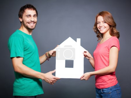 Couple showing paper house