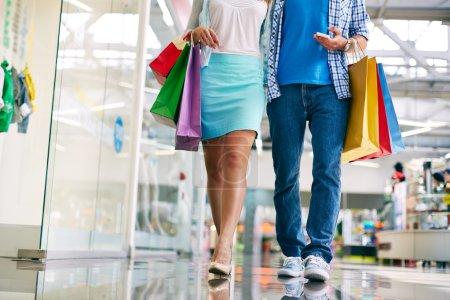 Photo pour Jambes de jeune couple d'acheteurs marchant dans le centre commercial - image libre de droit