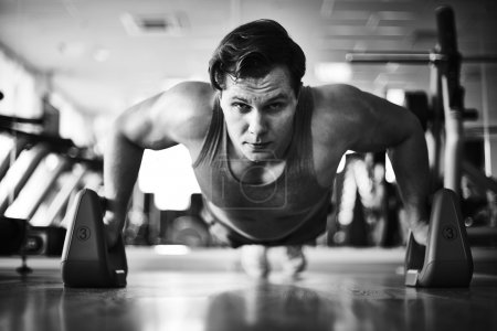 Photo pour Athlète faisant des exercices physiques sur le sol dans la salle de gym - image libre de droit