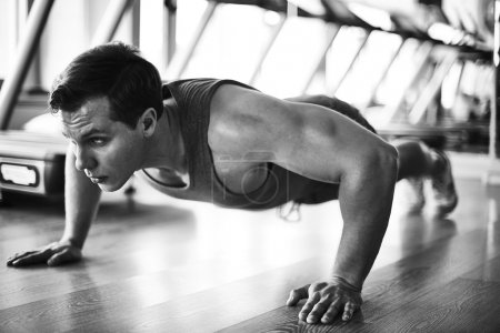 Photo for Sportive man doing physical exercises on the floor in gym - Royalty Free Image