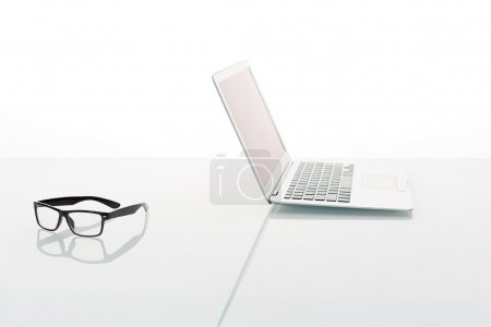 Laptop and glasses isolated