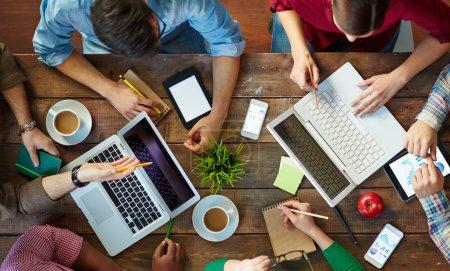 Photo pour Vue en angle élevé de personnes se réunissant à table et travaillant avec des ordinateurs portables et des pavés tactiles - image libre de droit