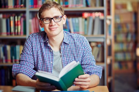 man sitting in library with book