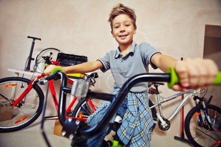 Photo pour Adolescent petit garçon en casual assis sur le vélo - image libre de droit