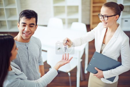 Realtor giving happy couple key