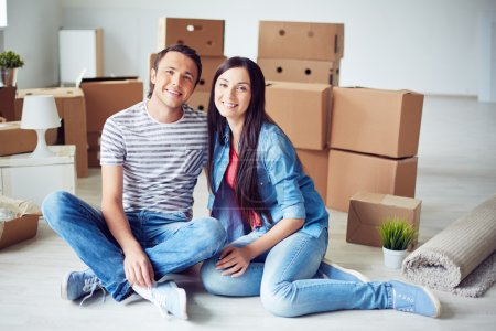 Man and woman sitting on the floor of new flat