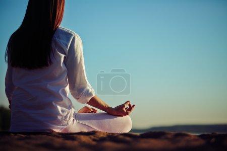 Photo pour Vue arrière de la femme méditante assise en pose de lotus contre le ciel bleu à l'extérieur - image libre de droit