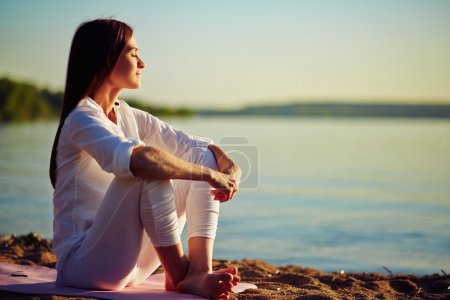 Serene woman sitting on sandy beach