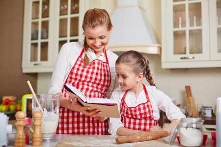 Girl and mother with cookery book