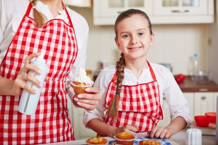 Photo for Mother and daughter cooking muffins with whipped cream in home kitchen - Royalty Free Image