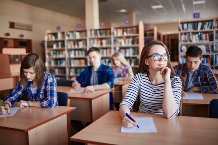Photo for Pensive girl sitting at the desk in working environment at lesson - Royalty Free Image