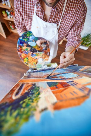 artist painting with paints on canvas