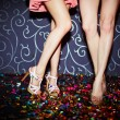 Legs of two girls dancing in night club, close up...