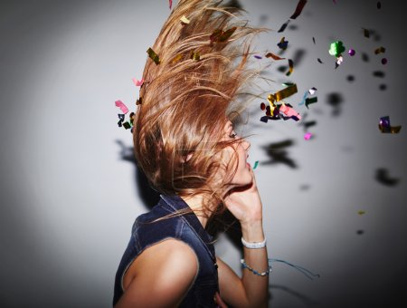 Photo for Energetic female dancer with confetti having fun in nightclub - Royalty Free Image