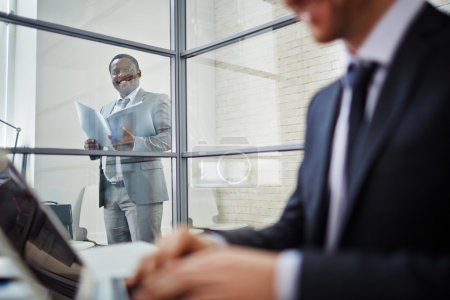 Photo for Confident businessman in suit looking at his working colleague in office - Royalty Free Image