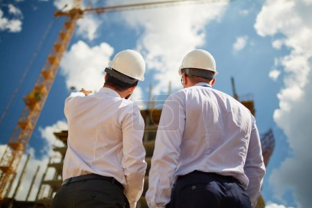 architects in helmets discussing new construction