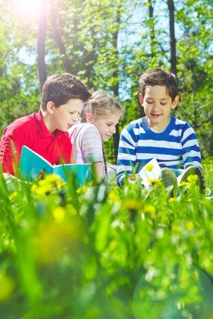 Photo pour Amis adorables lisant des livres ensemble dans le parc - image libre de droit