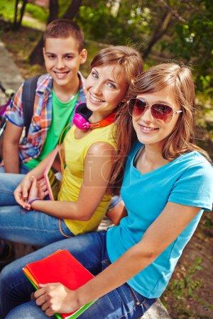 Friendly teens resting in park