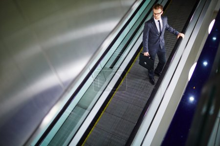Businessman with briefcase standing on escalator