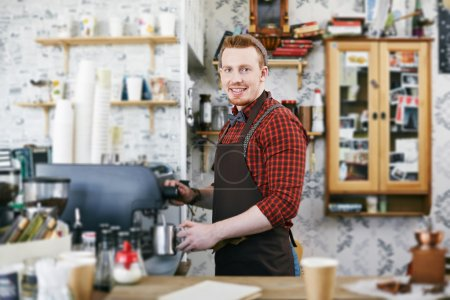 Photo for Happy barman in apron looking at camera while making coffee - Royalty Free Image
