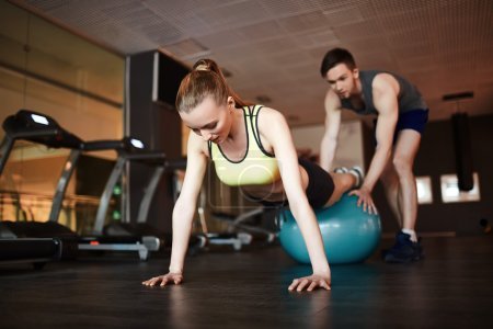 woman doing push ups on ball with trainer