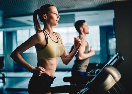 woman and man running on treadmill