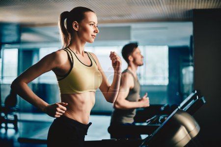 Photo for Active young woman and man running on treadmill in gym - Royalty Free Image