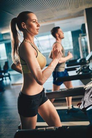 woman with earphones running on treadmill