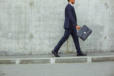 businessman in suit walking along concrete wall