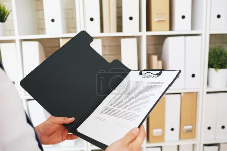 Photo for Businessman holding open folder with text of contract, close up - Royalty Free Image