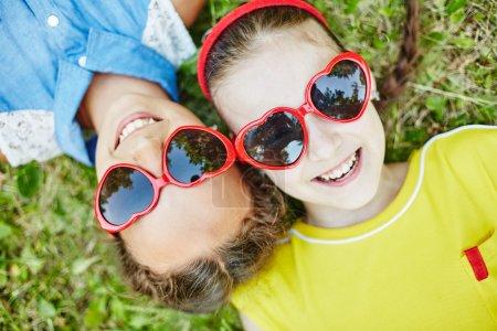 Photo pour Vue de dessus gros plan portrait de filles heureuses en forme de coeur lunettes de soleil regardant la caméra avec des sourires tout en se relaxant sur l'herbe verte - image libre de droit